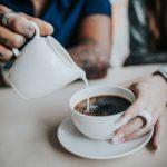 オシャレなコーヒーカップにミルクを注ぐ女の人