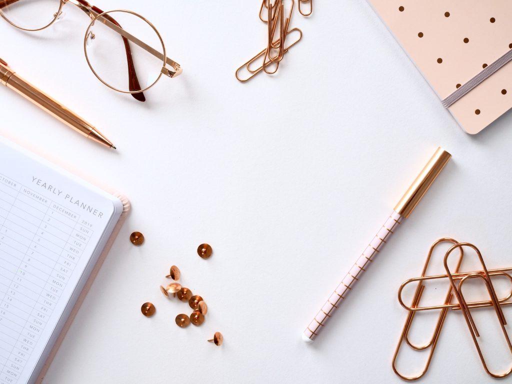 白い机の上のノートやペンなどの文房具