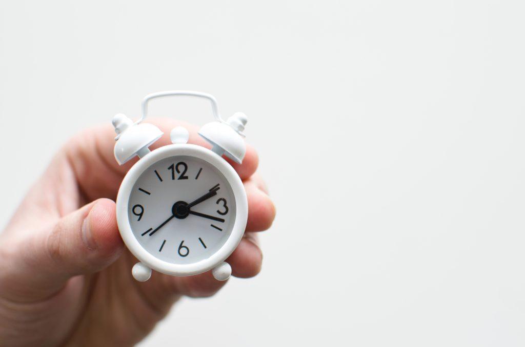 背景は白い壁で人が白い小さな目覚まし時計をもっている