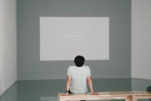 男の人が白いスクリーンを眺めている写真
