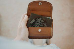 財布からスタバの顔をしたお金がでてきているところ
