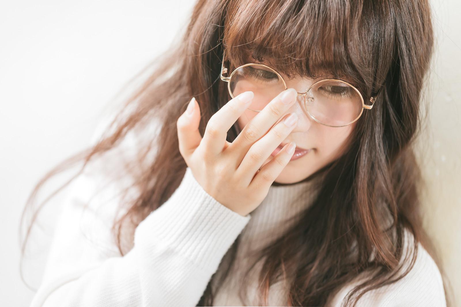 メガネをくいってしている女性