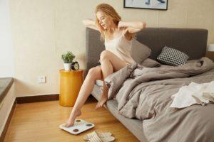 朝ベッドから女の人が眠そうに起床している