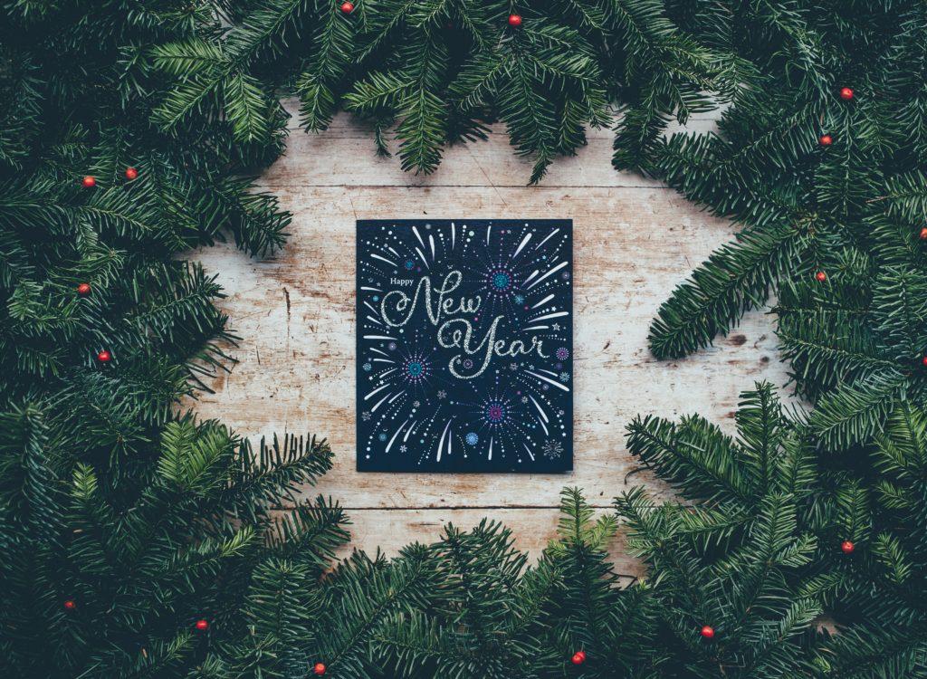 NewYearと書かれたカードの周りに緑の木の枝