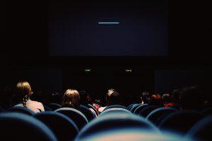 映画館でいろんな人が黒い画面をみてる