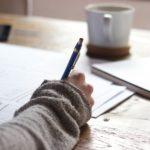 白い机で白いノートにシャープペンシルで勉強中
