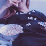 外国人の女の人がポップコーンを食べながら動画をみてぐうたらしている