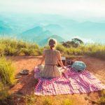 山の上に女の人がシートを広げて座っている