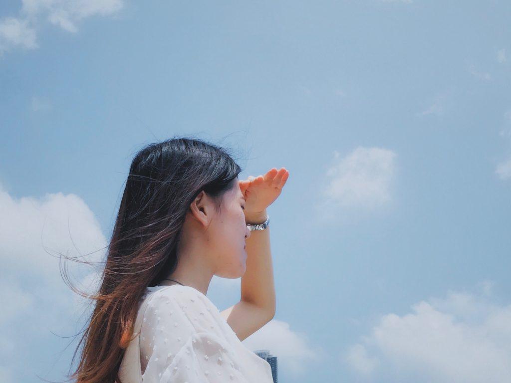 女の人が青い空の元でなにかを探している